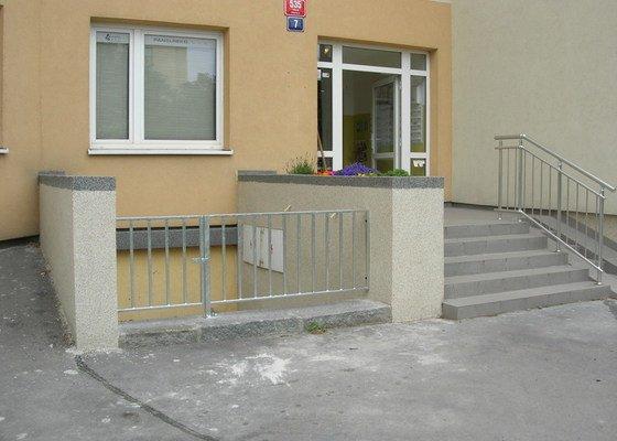 Kovové zábradlí před panelovým domem