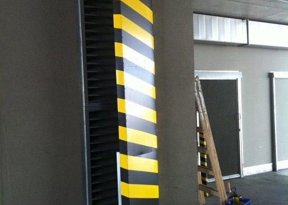 Bezpečnostní nátěr na  hlukových zástěnách .Povrch :podklad žlutá,šikmé černé pruhy v areálu Prosek Point,Prosecká 851/64,Praha 9.