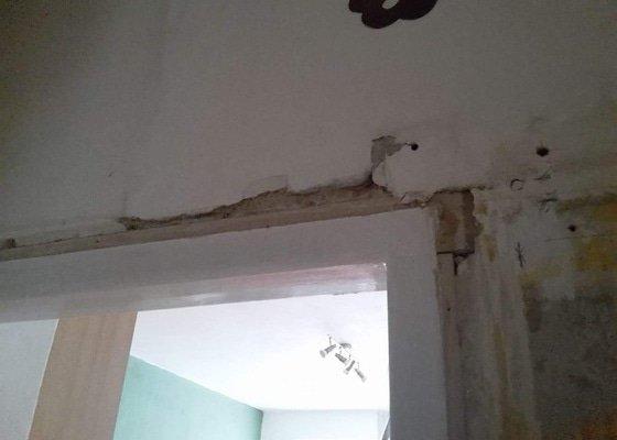 Přezdění vydrolené omítky okolo dveří, srovnání zdi, odstranění dřevěných futer + vyzdění otvoru, olištování dřevěných futer dveří