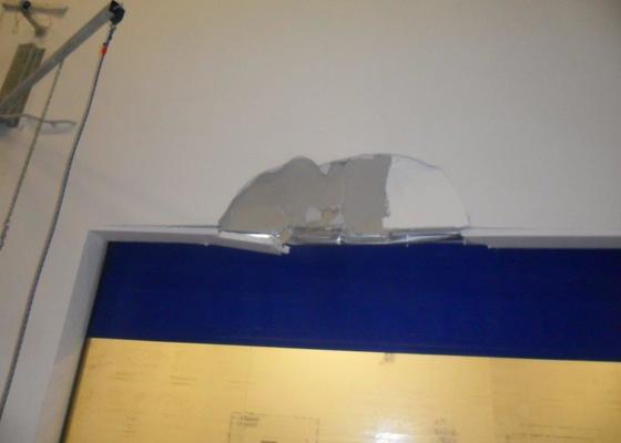 Oprava sádrokartonové stěny nad vratovým otvorem.