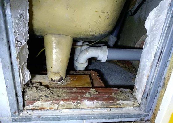Instalatér zedník, teče voda z trubek pod vanou
