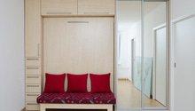 Kuchyňská linka a úložná skříň s vyklápěcí postelí a sedačkou.